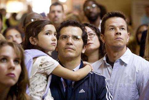 Jess (Ashlyn Sanchez, left), her father Julian (John Leguizamo) and Elliot (Mark Wahlberg) watch the latest news about a widening crisis. Photo credit: Zade Rosenthal